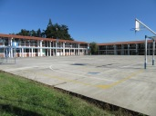 La cancha (basketball court), and more of the school.
